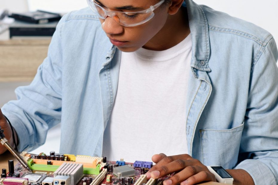 teen wearing safety goggles soldering computer parts